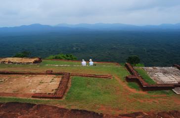 Couple are sitting on the upper palace Sigiriya, Sri Lanka
