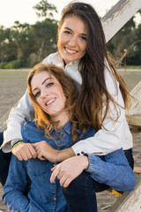 Female Best Friends Sitting on Wooden Stairs.