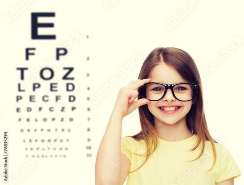 smiling cute little girl in black eyeglasses - 76835294