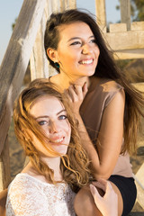 Pretty Female Friends Sitting on Wooden Stairs.