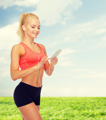 smiling sporty woman with smartphone and earphones