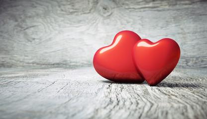 2 rote Herzen auf Holzhintergrund