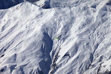 Off-piste slope and paraglider in nice day