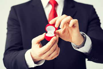 man with wedding ring and gift box