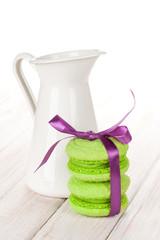Green macarons with purple ribbon and milk jug