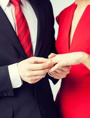 man putting  wedding ring on woman hand