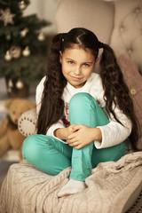 Маленькая девочка улыбается и сидит на стуле