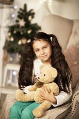Маленькая девочка улыбается и сидит в кресле с плюшевым мишкой