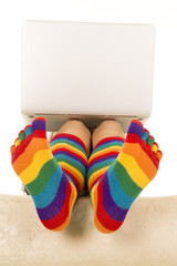 feet in colored socks under laptop