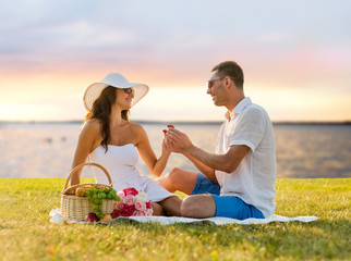 smiling couple with small red gift box on picnic