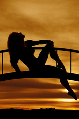 silhouette of a woman sitting lean back hold knee
