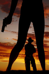 silhouette of woman legs with gun hold down cowboy