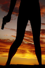 silhouette of woman legs with gun hold down