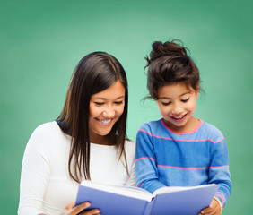 happy teacher and little school girl reading book