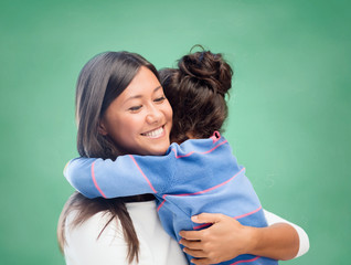 happy woman and little girl hugging at school