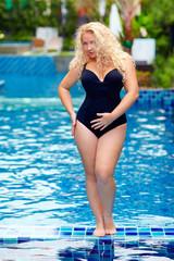 beautiful plus size woman posing in the pool