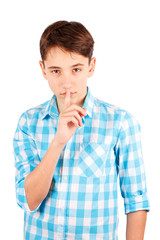 Serious teen boy in plaid shirt holding finger on lips