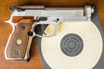 Target shooting, the gun and the target with the knife on the ta