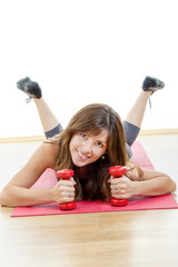 girl with weights or dumbbells wearing sports clothing lying on