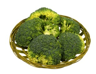 Fresh broccoli in a green basket over white