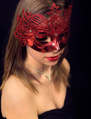Beautiful girl in a carnival mask on a black background