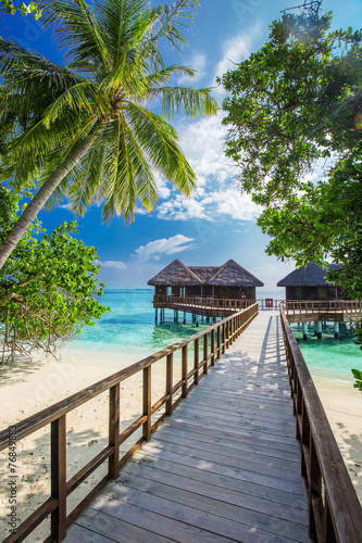 Bridge leading to overwater bungalow in blue lagoon