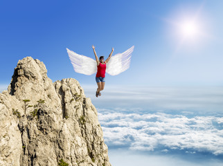 Girl flies on the wings against the background of clouds and mou