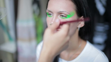 Visagiste makes makeup,  makeup artist tints the model's eye,