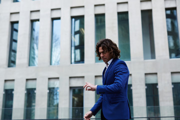 Young business man checking time while walking on city street