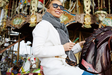 Attractive woman enjoying time riding on a merry go round