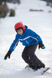 Young boy riding snowboard