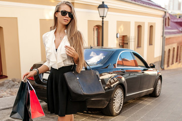 Beautiful woman goes shopping in the city with car