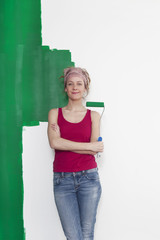 Frau mit Farbrolle vor Wand