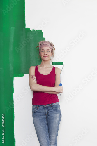 canvas print picture Frau mit Farbrolle vor Wand