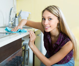 Maid cleaning furniture in kitchen