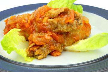 Greek juicy fish on green lettuce