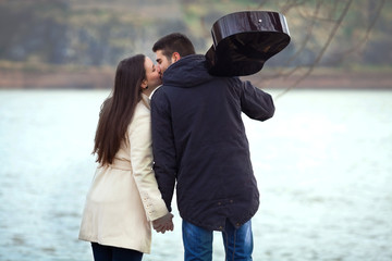 Romantic young couple kissing by the river