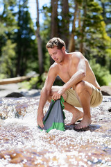 Camping man hiking washing laundry in nature river