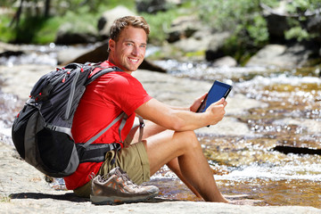 Tablet hiking man reading ebook or map in nature