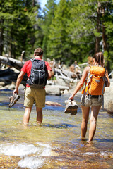 Hikers group walking barefoot crossing river