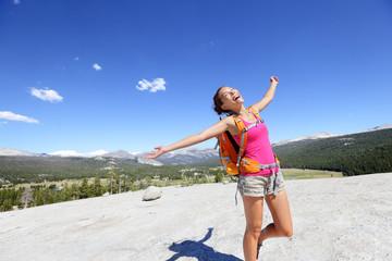 Happy hiking woman dancing in mountain landscape