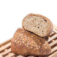 whole grain bread cut in half on wooden cutting board over white