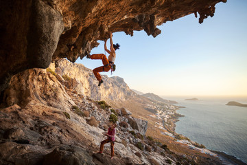 Young woman climbing on cliff, female partner belaying