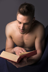 Shirtless athletic young man reading big book