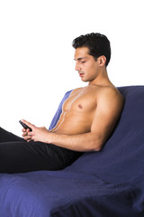Shirtless young man using cell phone to type text message