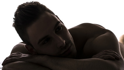 Chiaroscuro shot of cute young man naked resting