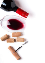 Bottle, glass with red wine, corks and corkscrew
