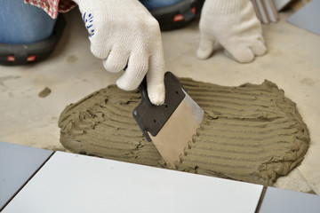 Spreading cement during tiled floor installation