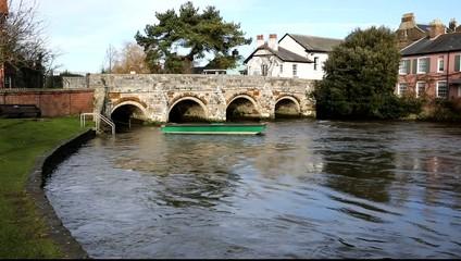 River Avon flowing Christchurch Dorset England UK with bridge