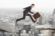 Businessman jumping over rocks